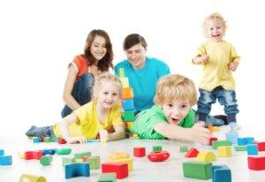 Szülők előtt három gyerek játszik vidáman.