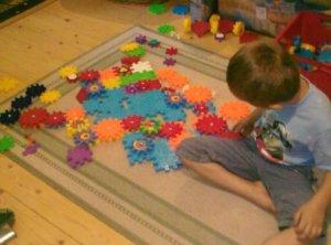 Fiu játszik színes összeszerelhető formákkal