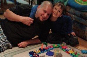 Apa-fia boldogan mosolyog a játékok közt