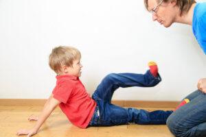 Kisfiú földön ülve lábával rúg apja felé